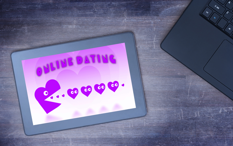Online dating on a tablet - concept of love, purple pacman eating hearts