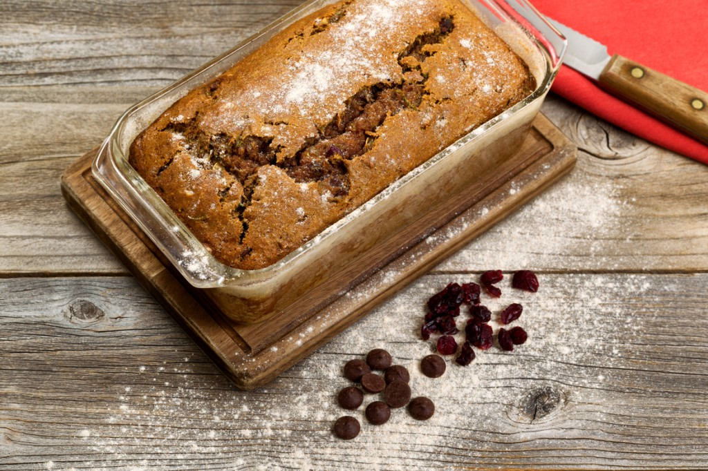 Freshly baked homemade zucchini bread in glass pan with knife and cloth napkin on rustic wood.